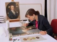 Diplom-Restauratorin Maike Behrends bei der Arbeit an Louise Seidlers Porträt der Ottilie Arnoldi, im Hintergrund J. F. A. Tischbeins Porträt Hufelands